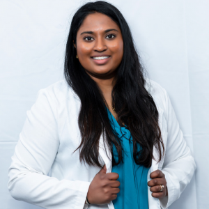 Dr Pavithra Nantheeswarar, dentist at Sandhurst Family Dental Clinic, is wearing a white coat and stands in front of a white background.
