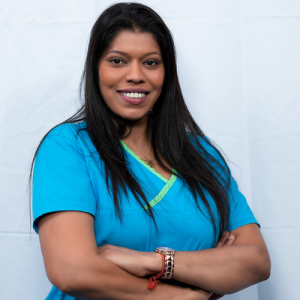 Suba, the office administrator at Sandhurst Family Dental Clinic, located in Scarborough, stands in blue scrubs with her arms crossed while smiling and posing in a welcoming stance.