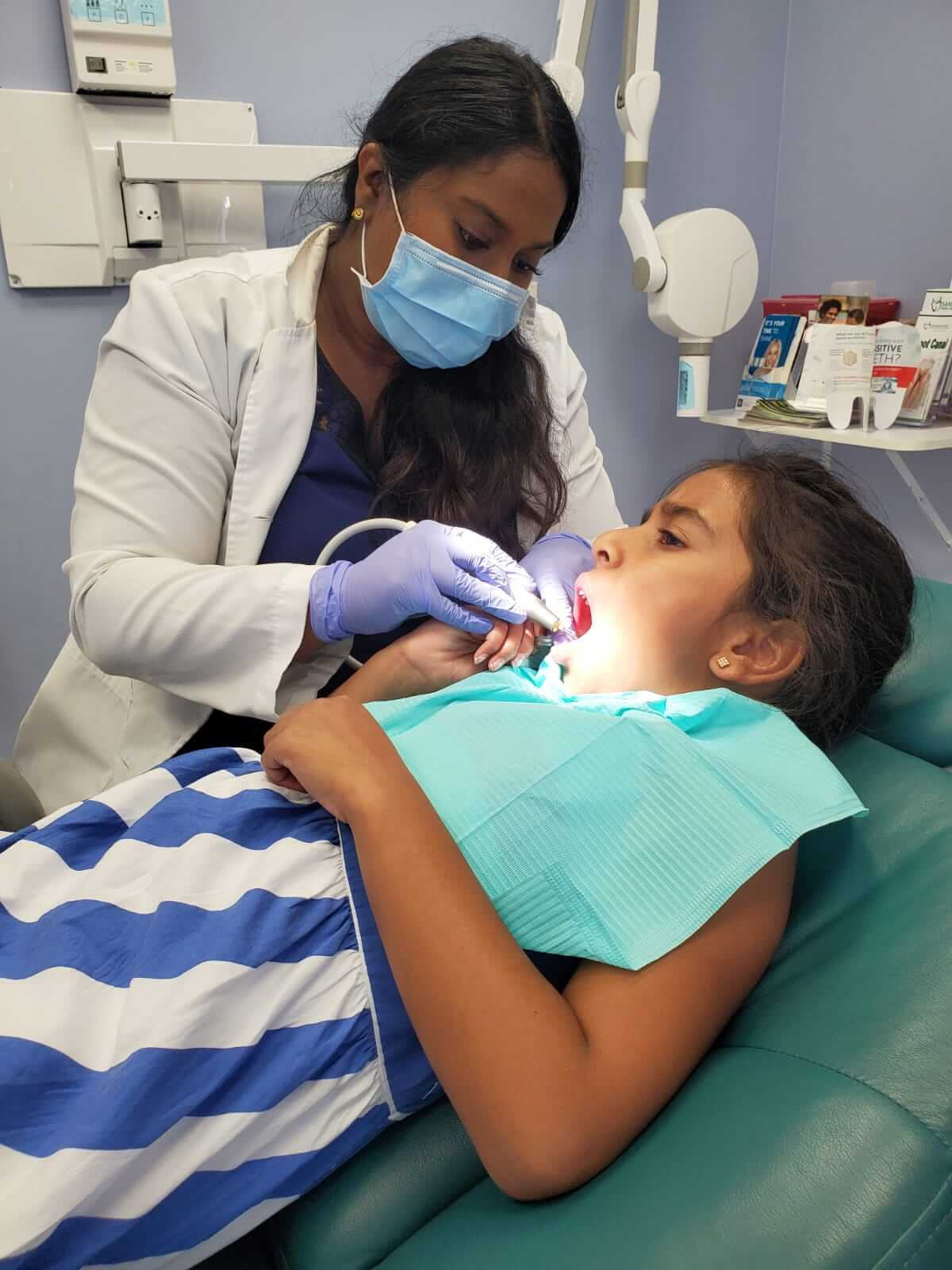 Dr. Pavithra Nantheeswarar, a dentist, provides dental services for a young patient, an adolescent girl at a family dental clinic.